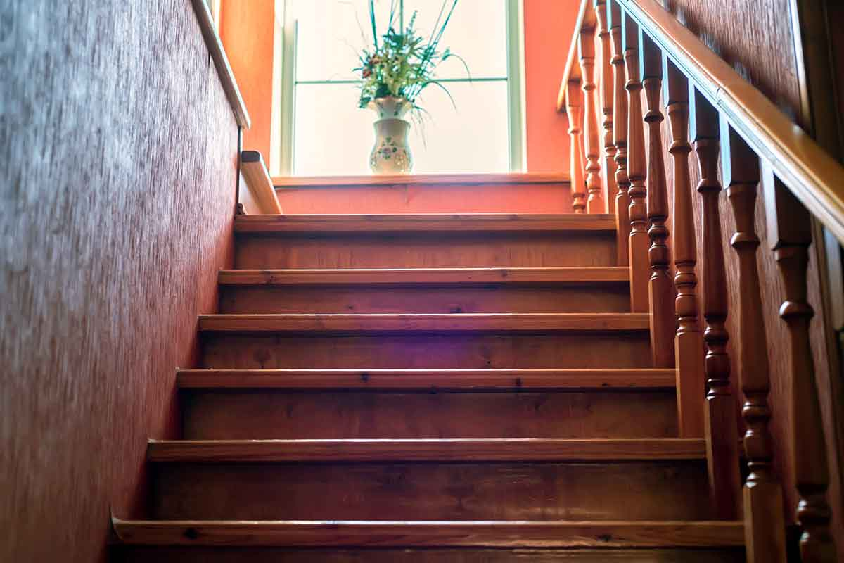 view up a brown wooden staircase with handrail