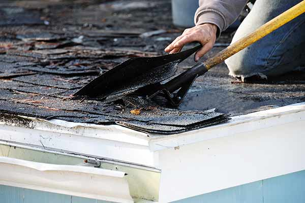 man repairing damaged roof shingles