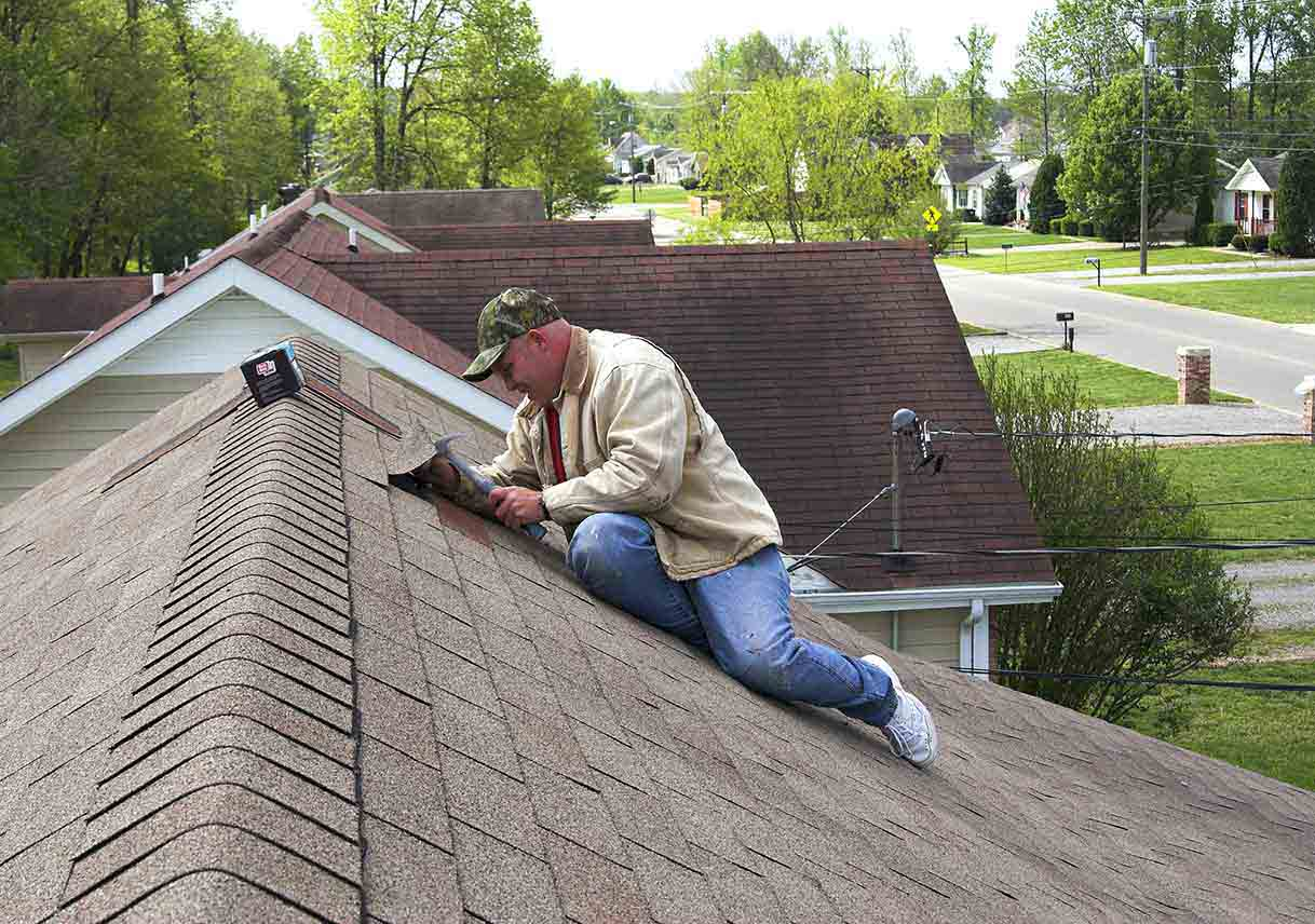 roofer repairing damaged shingles