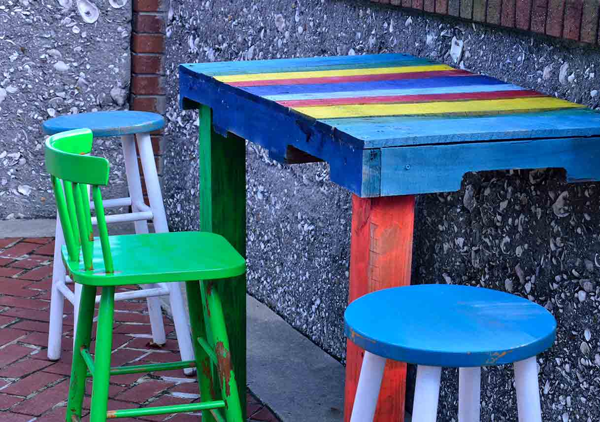 A bar and stool painted in bright colors sitting on a brick and tabby patio