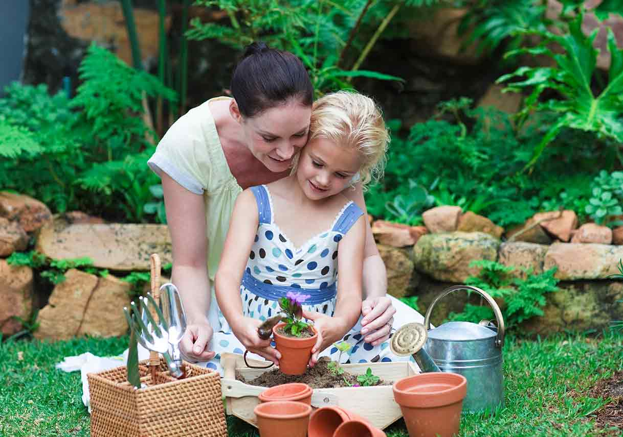 mother and daughter potting plants outside