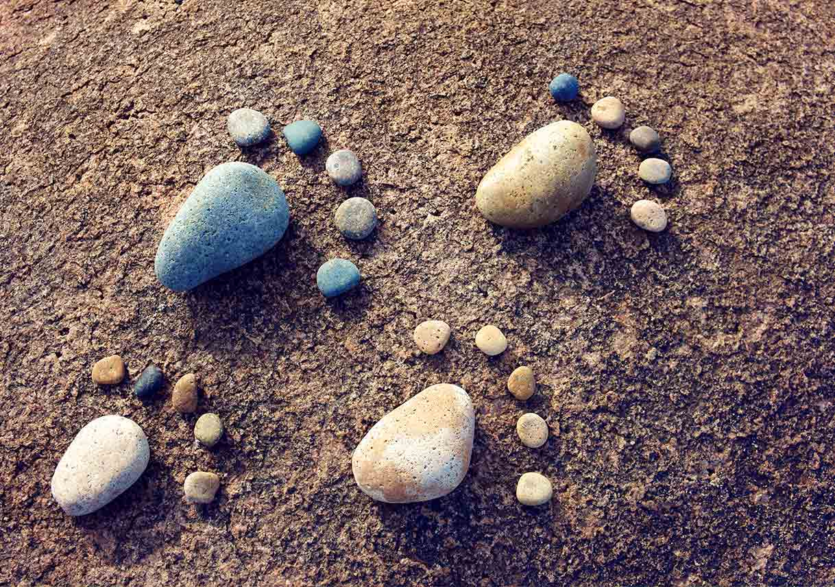 pebbles arranged into feet