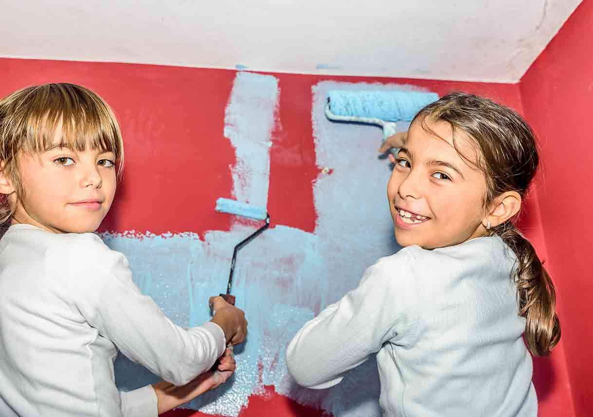 two young girls painting a wall