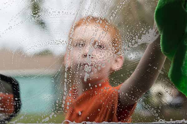 closeup of a boy washing a window