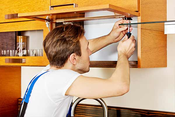 handyman repairing a cabinet