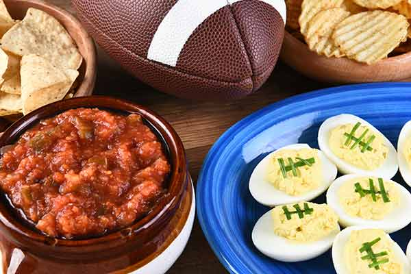 closeup of snacks on a table surrounding a football