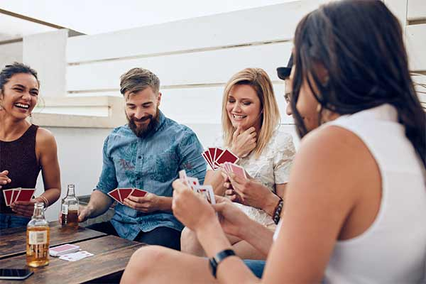 group of friends sitting at a wooden table playing cards during a party