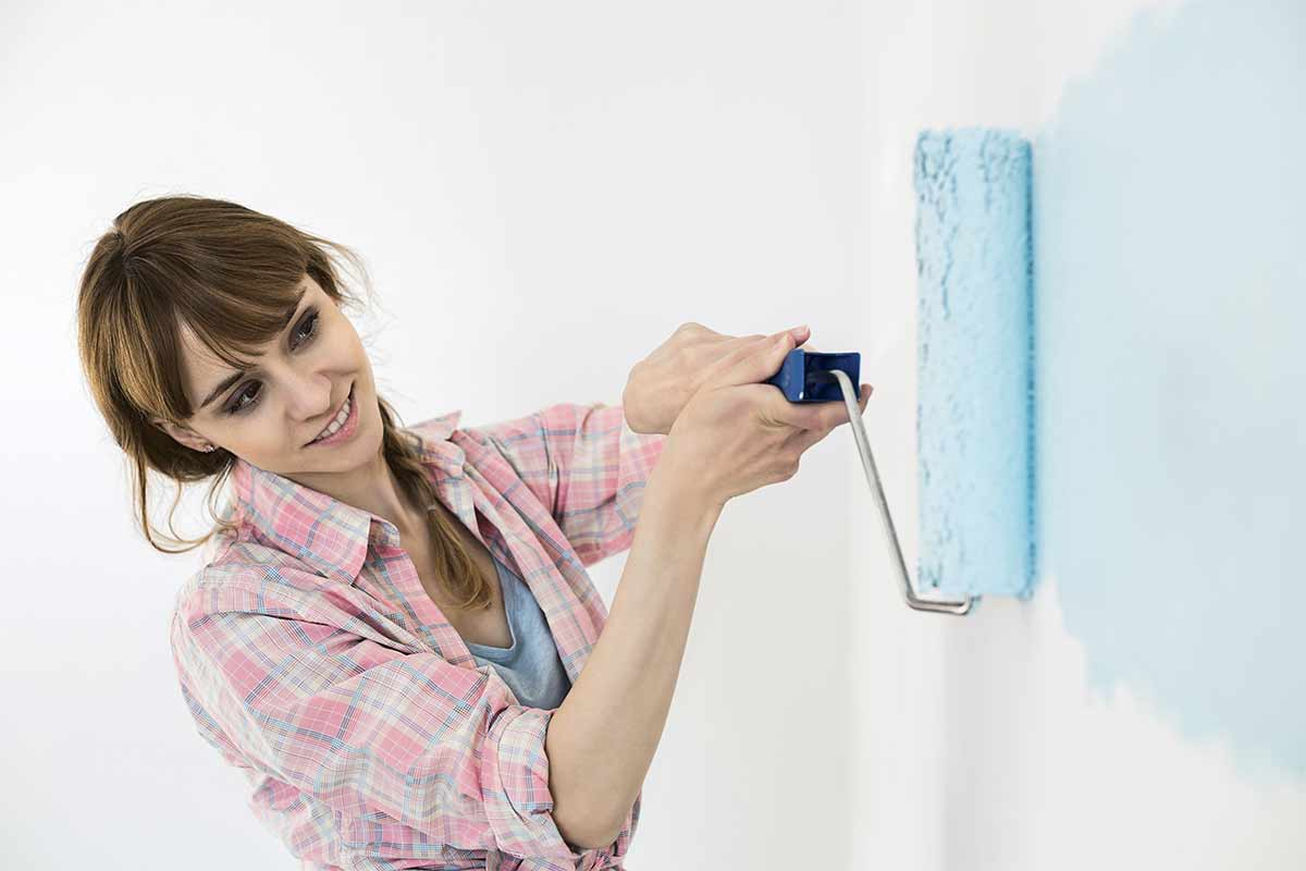 homeowner painting sample color on walls