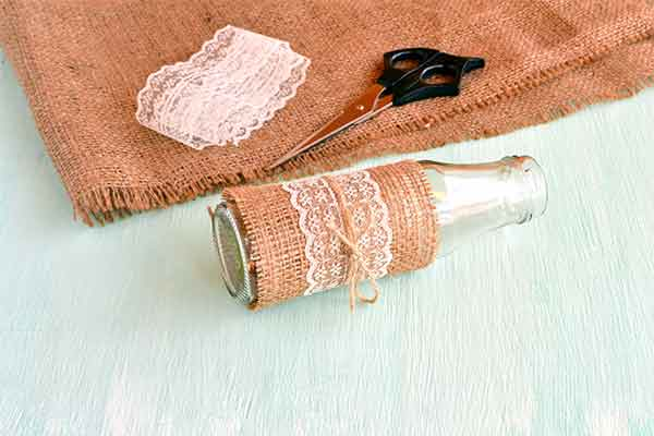 burlap with scissors and lace on top next to a crafty vase