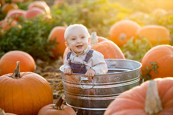 pumpkins surrounding boy in a tub