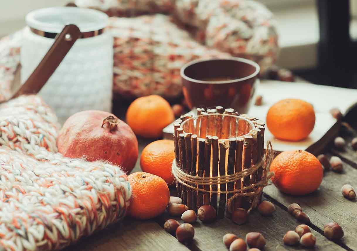 closeup of fruits, nuts, and a candle decorating a table