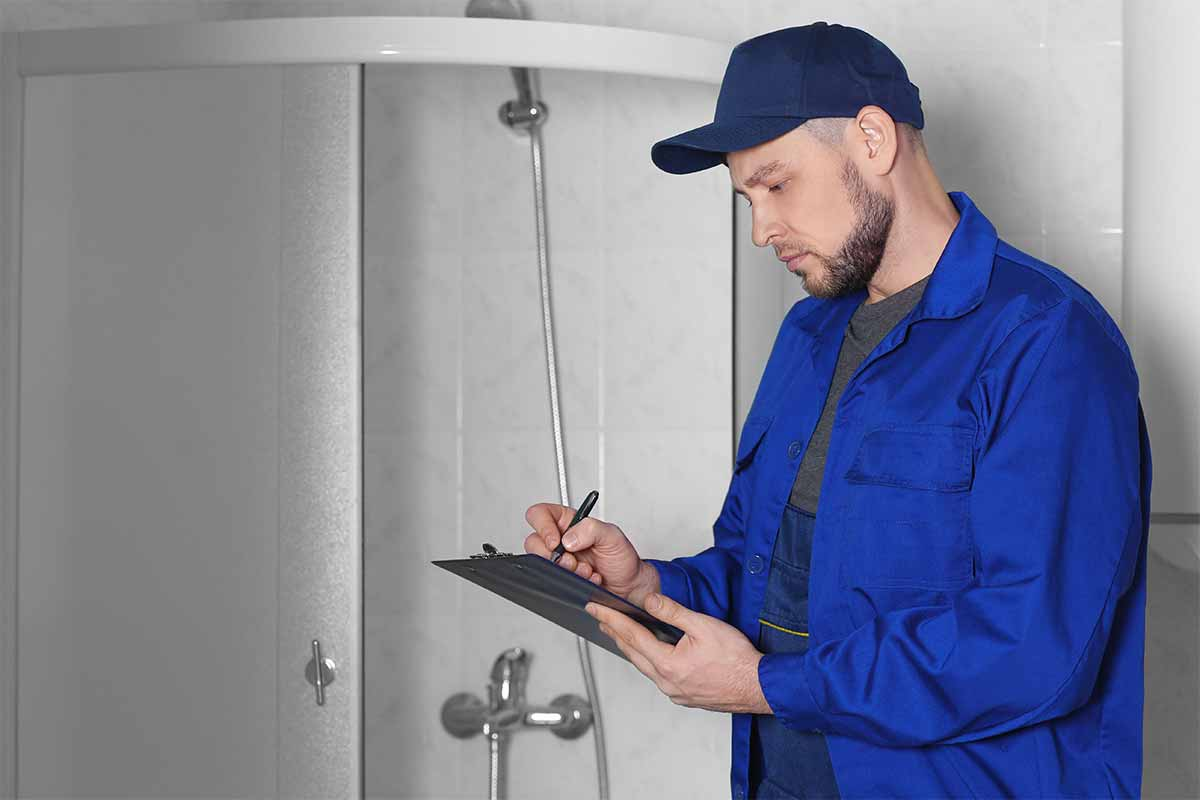 professional plumber assessing completed shower installation