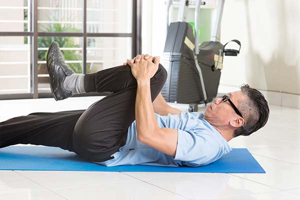 older man on exercise mat by workout equipment