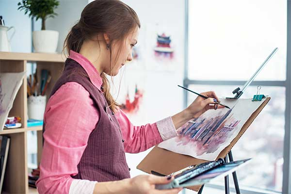 woman painting with stored art supplies at home