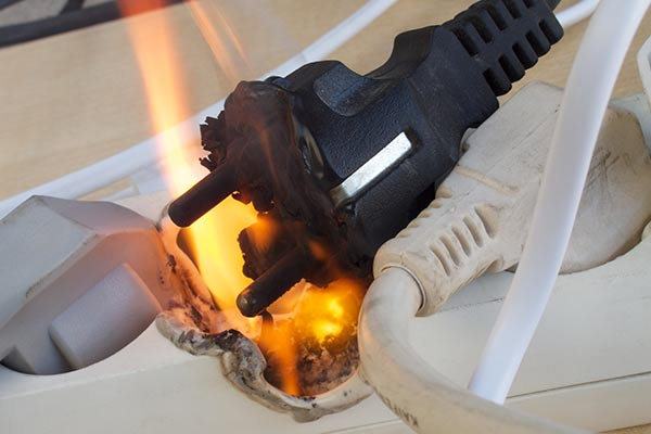 An electrical fire erupts from within a power strip