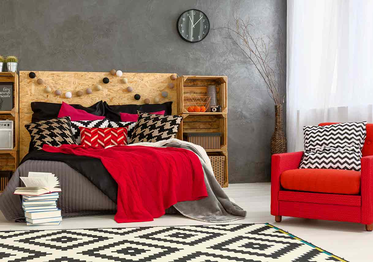 black, white, and red decorated bedroom with pillows and carpets in various patterns