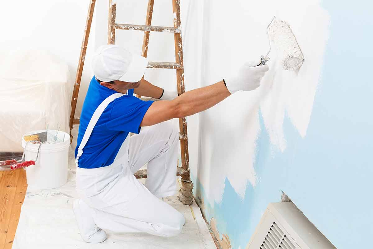 professional painter using water-based paint to paint a wall