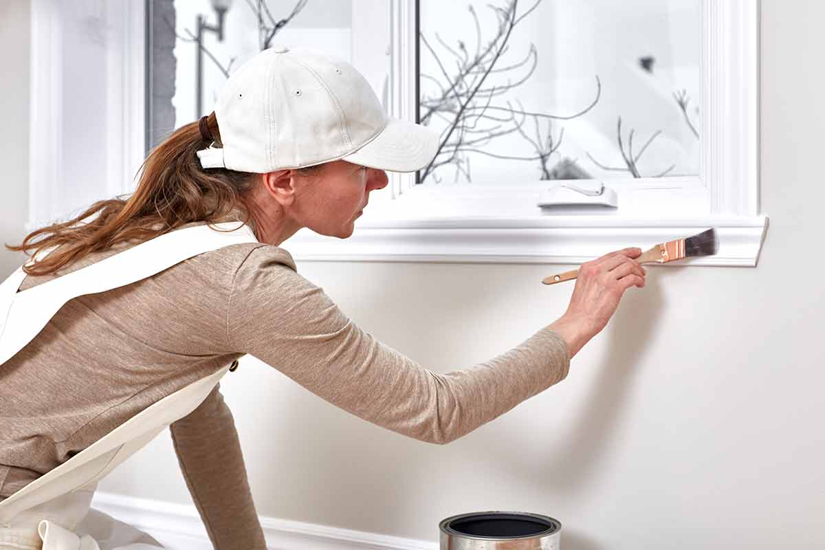 woman painting window trim with oil-based point