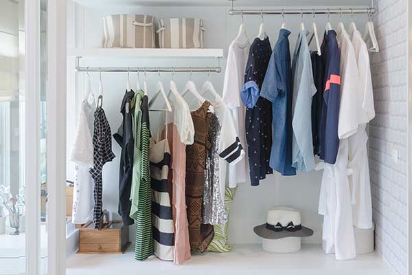 A white walled closet, filled with female apparel