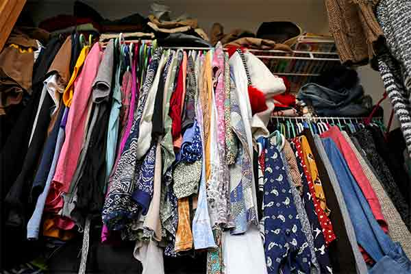 a woman's closet, cluttered with items