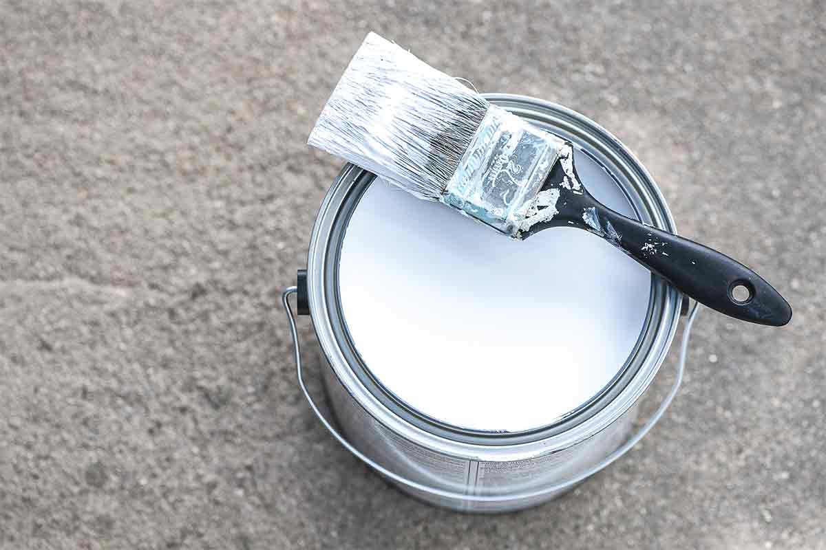 can of paint primer with brush