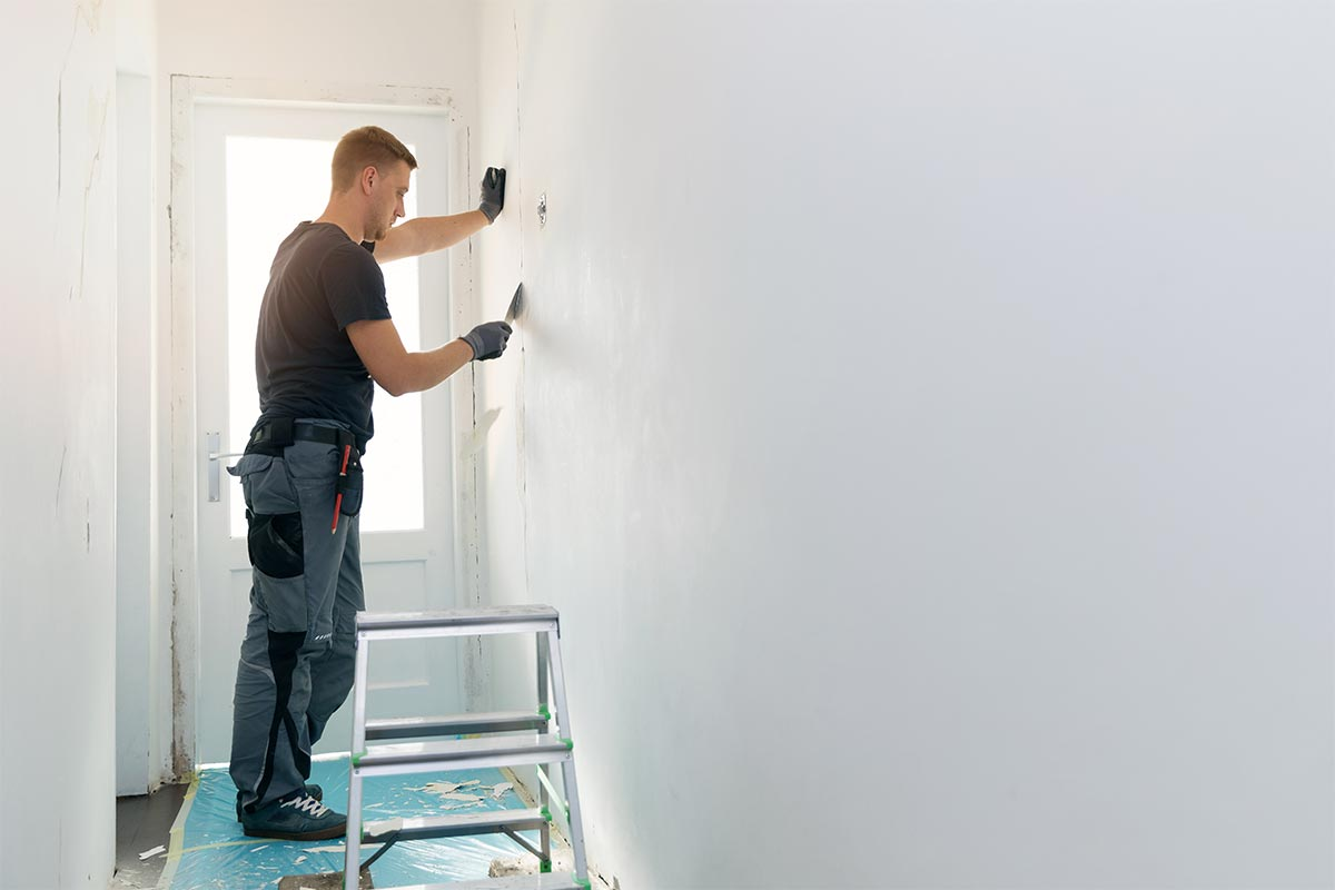 painter prepping wall for painting