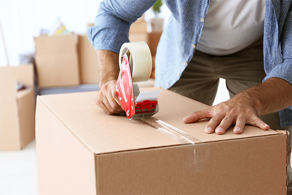 homeowner packing a moving box