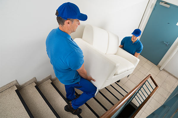 professional movers carrying sofa down set of stairs