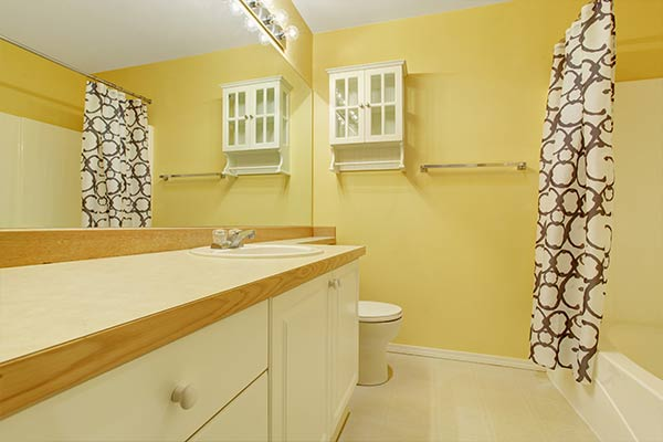 yellow bathroom with a wooden countertop