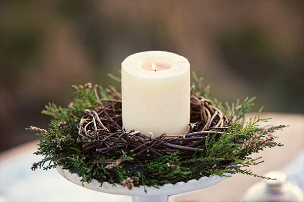 white candle wreathed with pine leafs and twigs