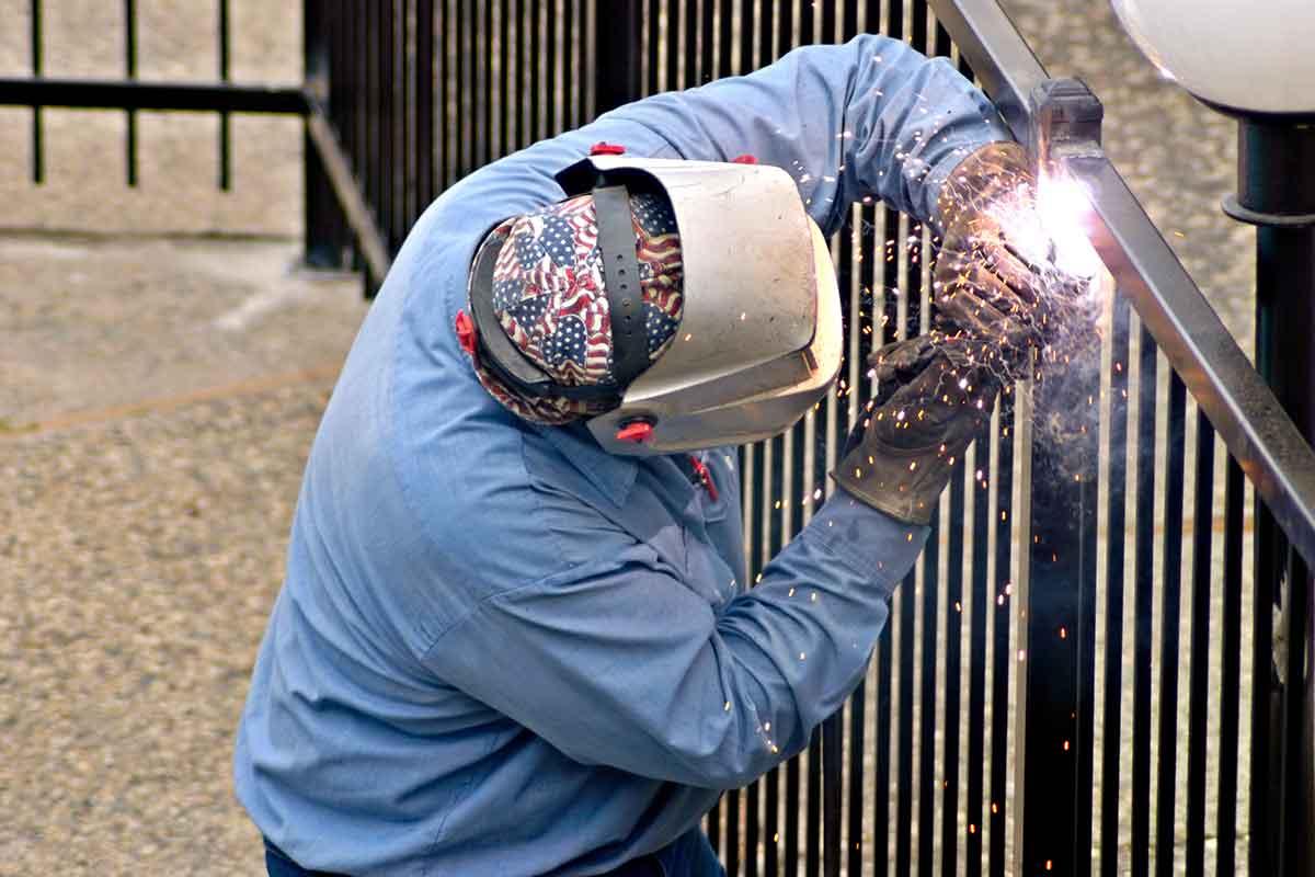 welder installing a metal fence