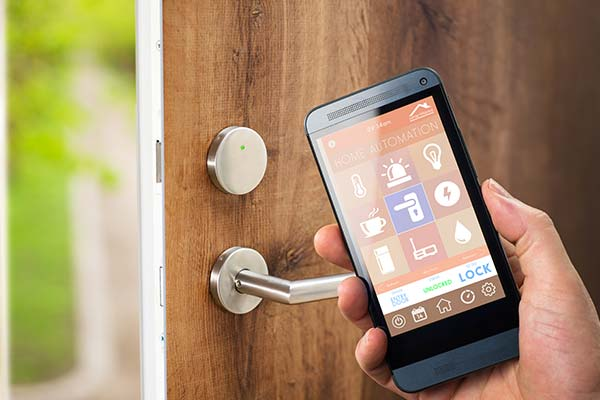 smart home app on cell phone in front of unlocked door