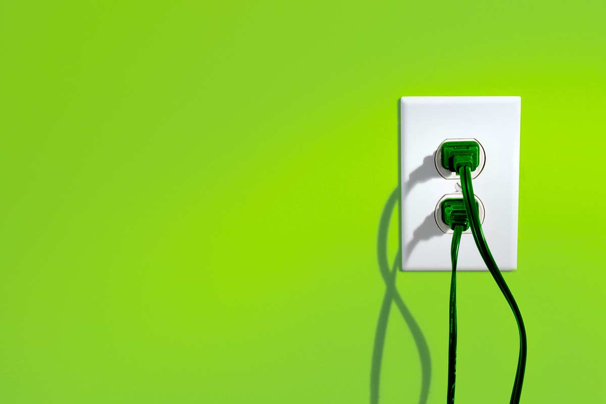 power cords plugged into outlet on a green wall
