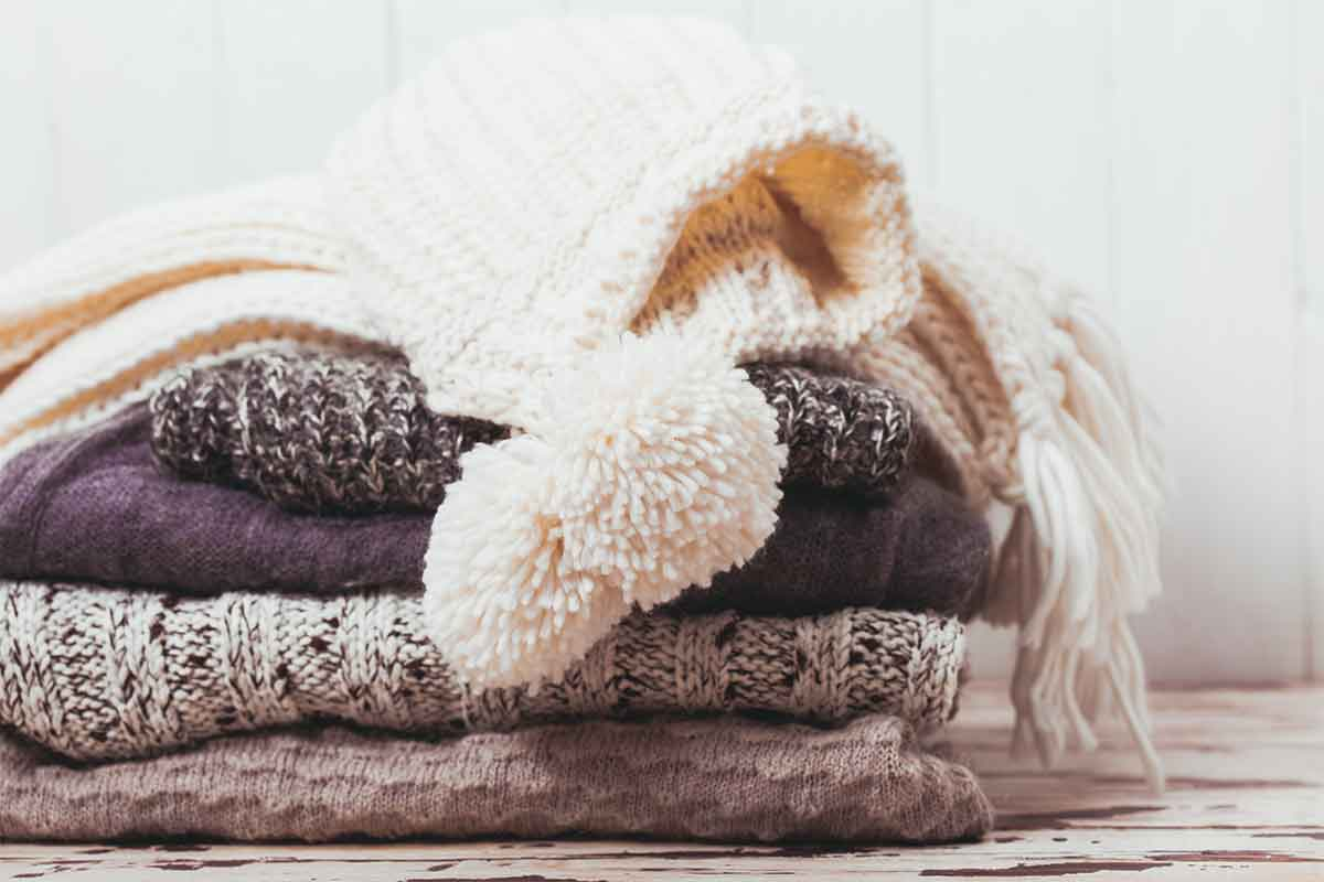 stack of folded sweaters and hats