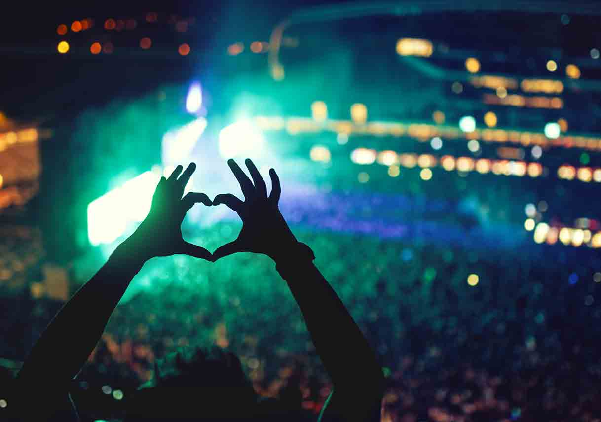 hands held up in the shape of a heart at a concert