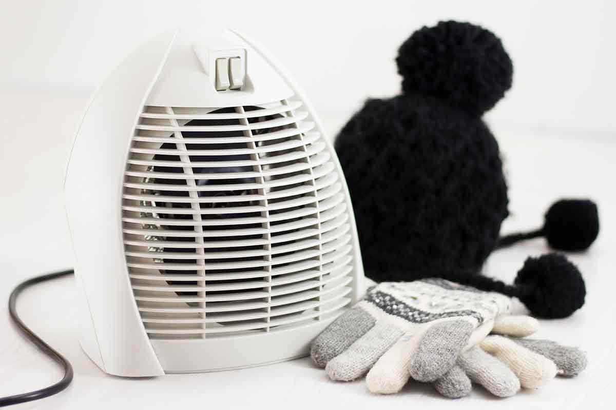 Photo of white electric space heater with knit hat and gloves next to it