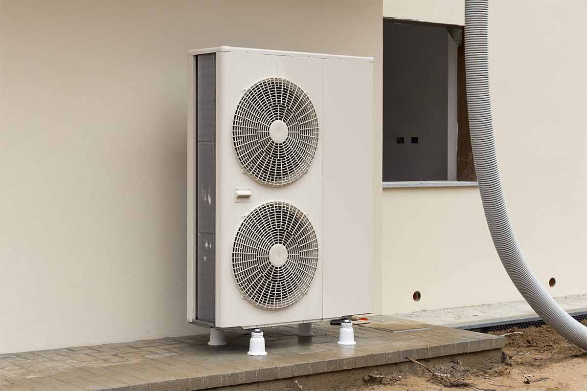 Heat pump outside of white stucco home