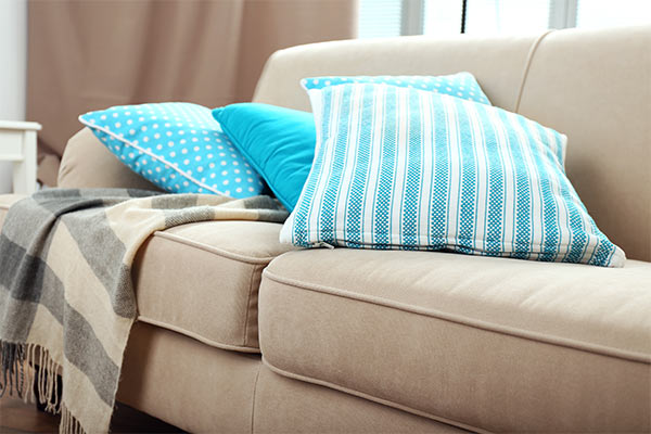 blanket and pillows on beige couch
