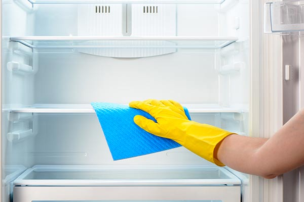 yellow gloved hand wipes down empty fridge with rag