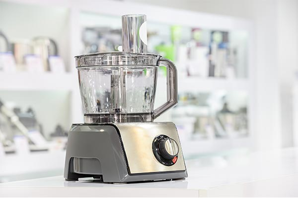 stainless steel food processor on a white counter top
