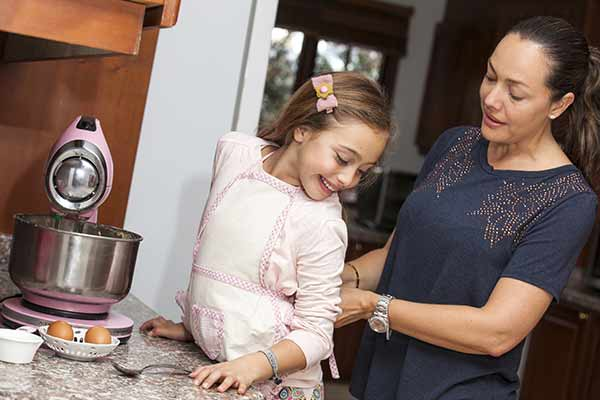 mom tying daughter's apron in front of mixer
