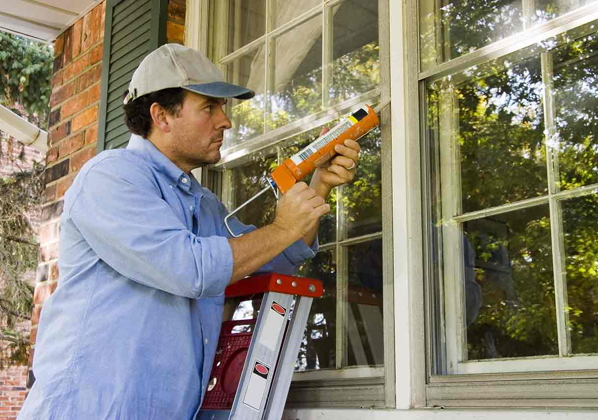 man on ladder caulking window