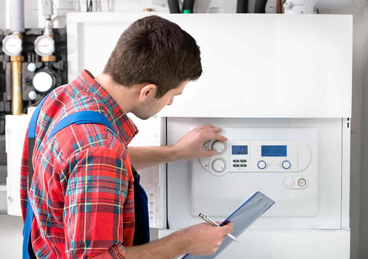 technician adjusting hot water heater boiler