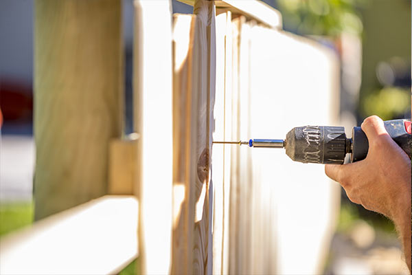 man working on a wooden fence with a drill