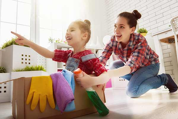 mother and daughter playing with cleaning supplies while cleaning at home