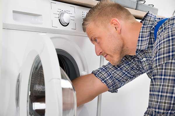 technician fixing inside of washing machine