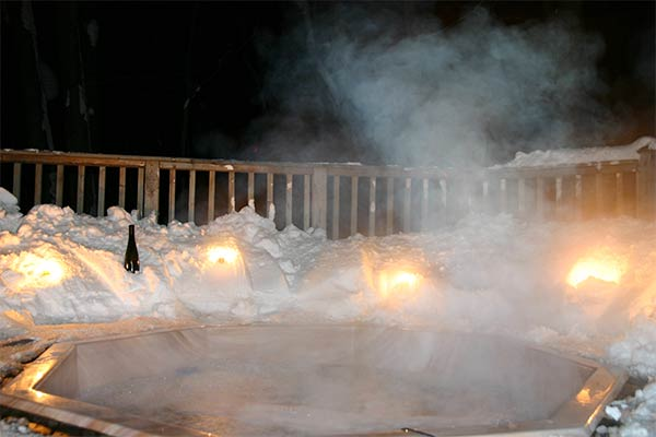 A hot tub wreathed in snow, under the night sky
