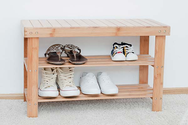 four pairs of shoes on wooden shoe shelf