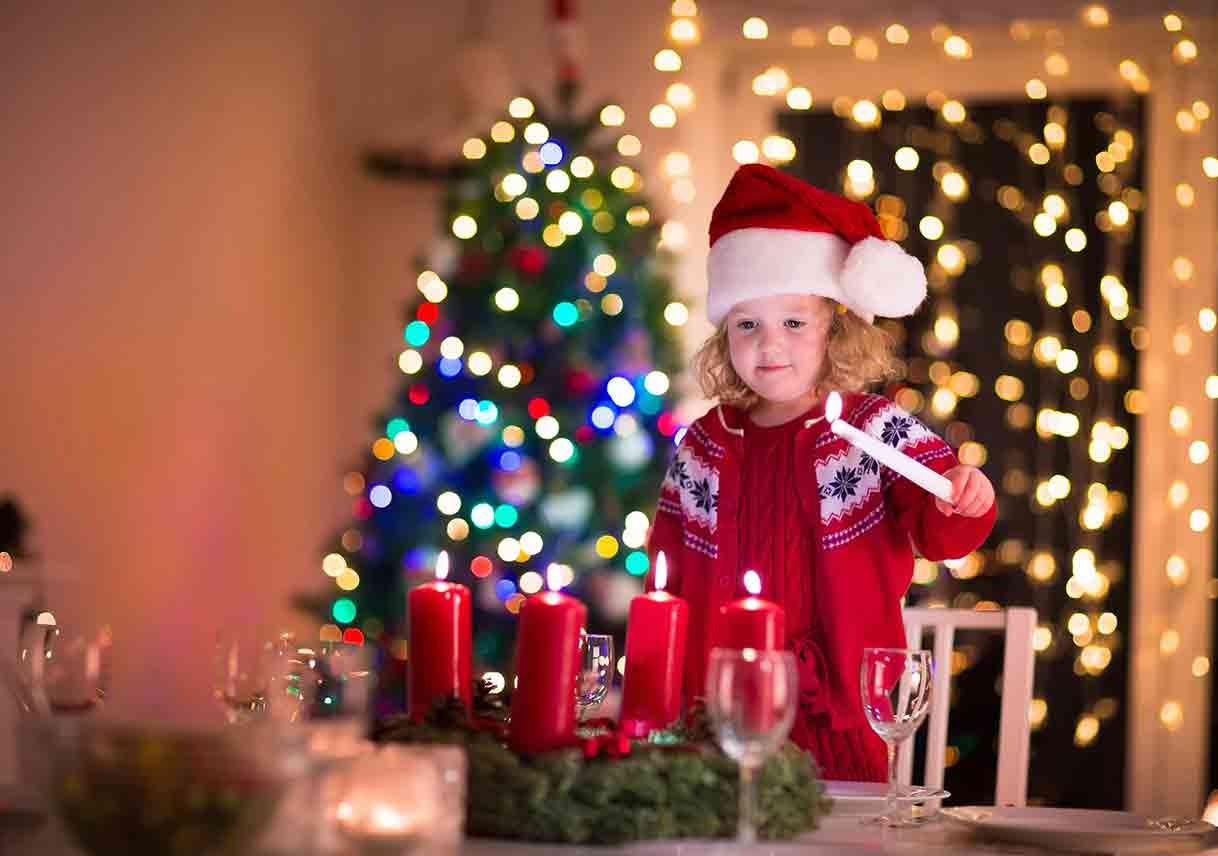 child lighting candles at Christmas table