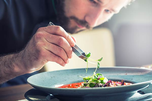chef decorating plate with herbs